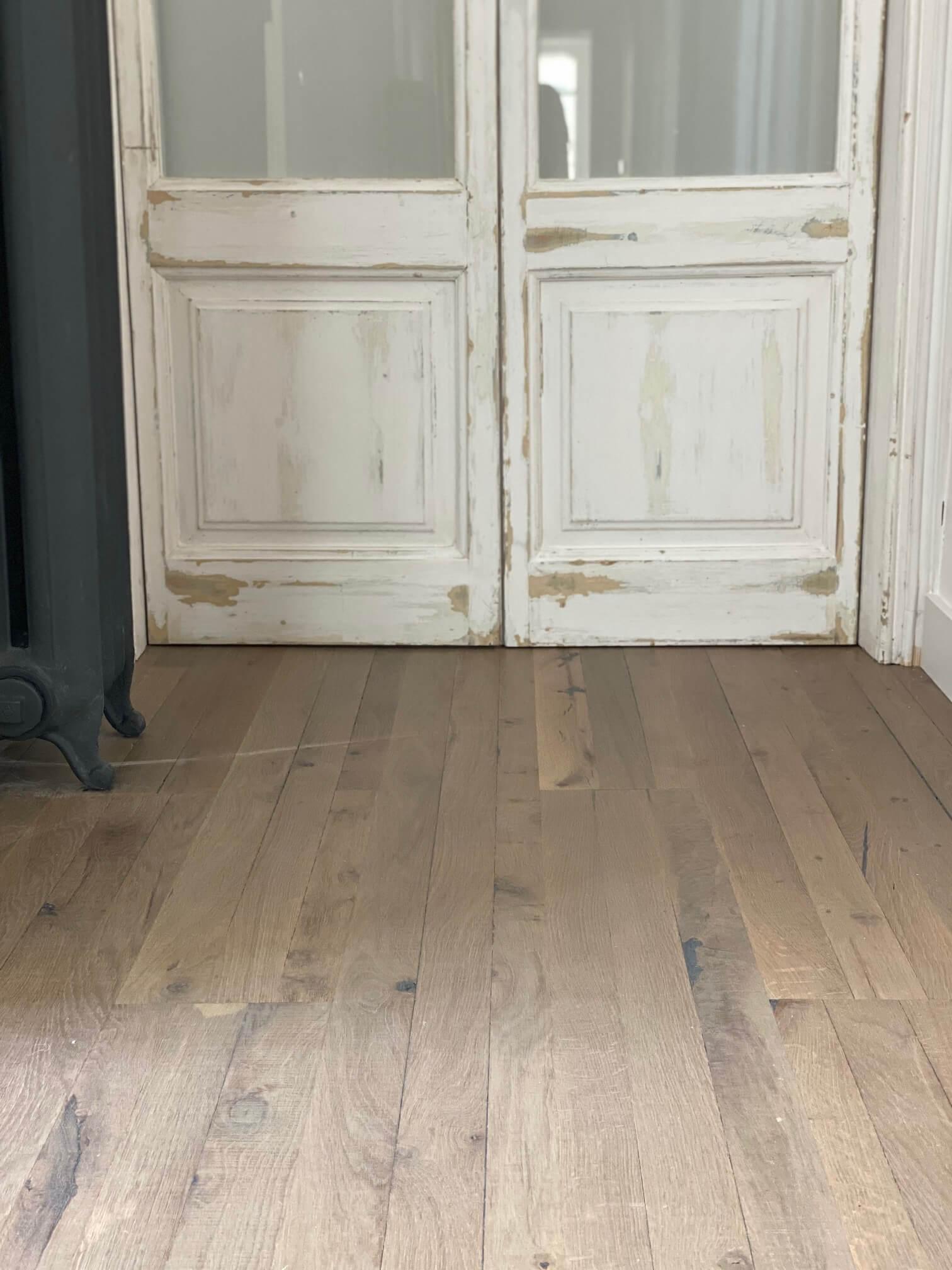 Primer plano del parquet de roble envejecido teñido gris WINco Triple 3074 en el pasillo de la vivienda