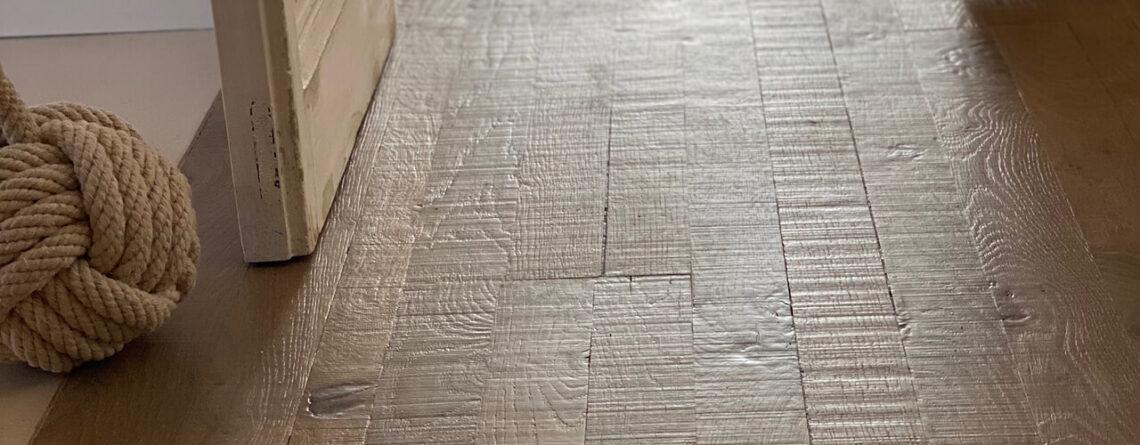 Primer plano del parquet de roble envejecido teñido gris WINco Triple 3074 en la habitación de la vivienda