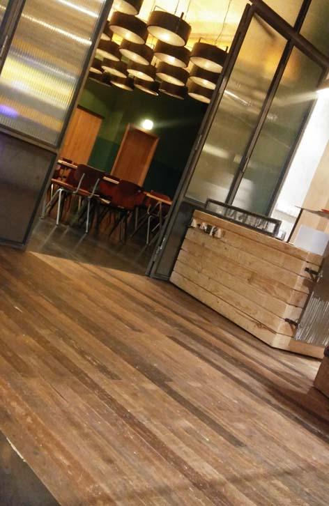 Detalle del suelo de madera recuperada WINco Imondi en la zona de vinos del restaurante La Caníbal de Madrid